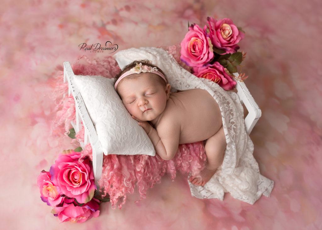 servizio fotografico newborn - neonata - fiori - lettino