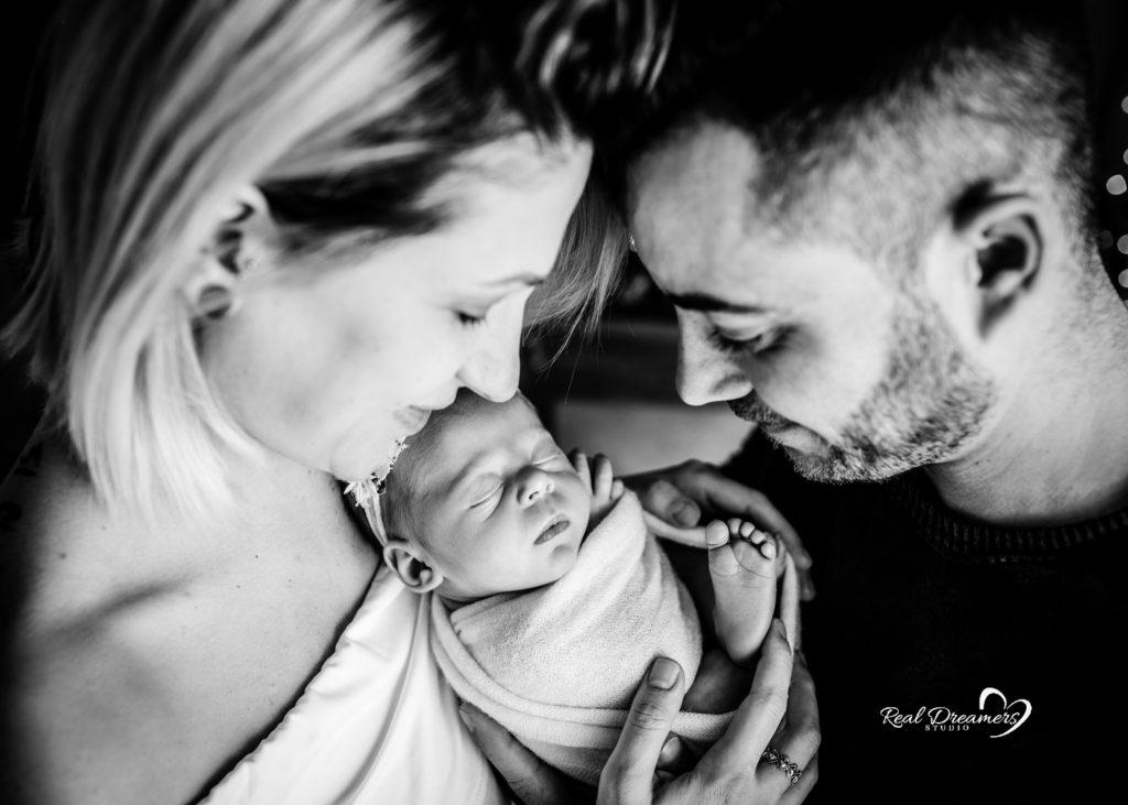cosa fare quando nasce un bambino mamma e papà guardano neonato