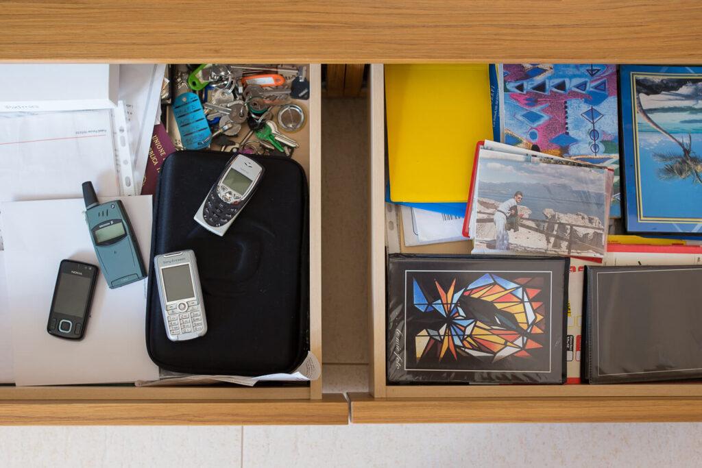 Quanto costa un servizio fotografico per bambini? Un cassetto aperto con delle foto dentro, ricordi preziosi e uaccanto un cassetto aperto con dei vecchi telefoni, cari ma senza valore